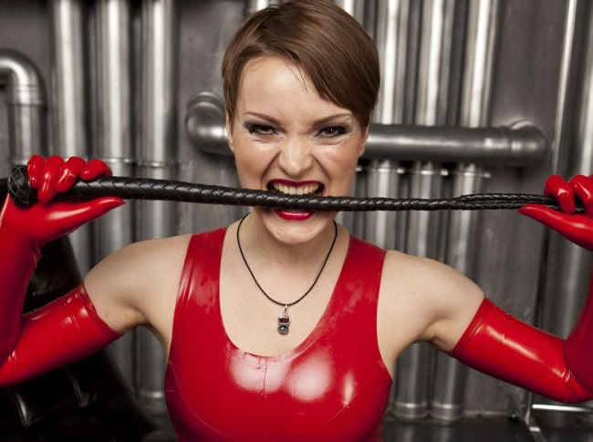 finacial domme in red latex gripping whip between teeth